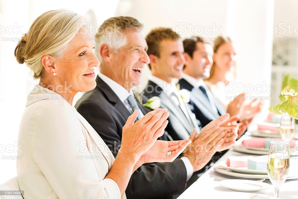Family And Guests Clapping At Table During Reception stock photo