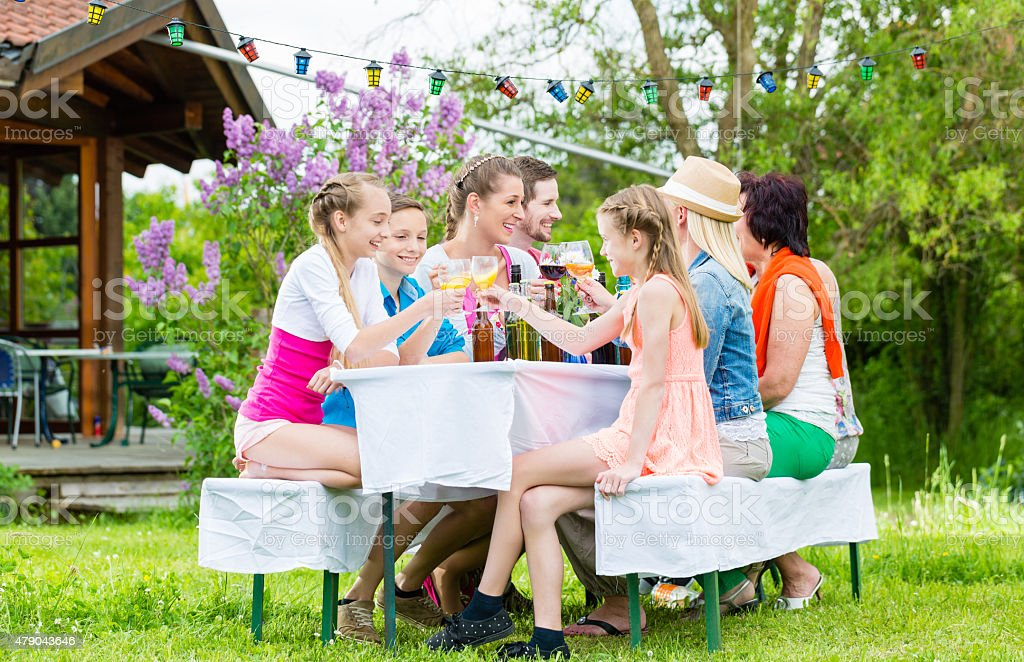 Family and neighbors at garden party drinking stock photo