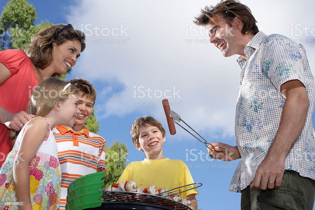 Family Around Grill In Garden stock photo