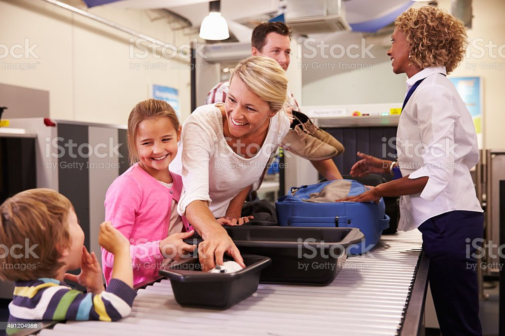 Family At Airport Passing Through Security Check stock photo