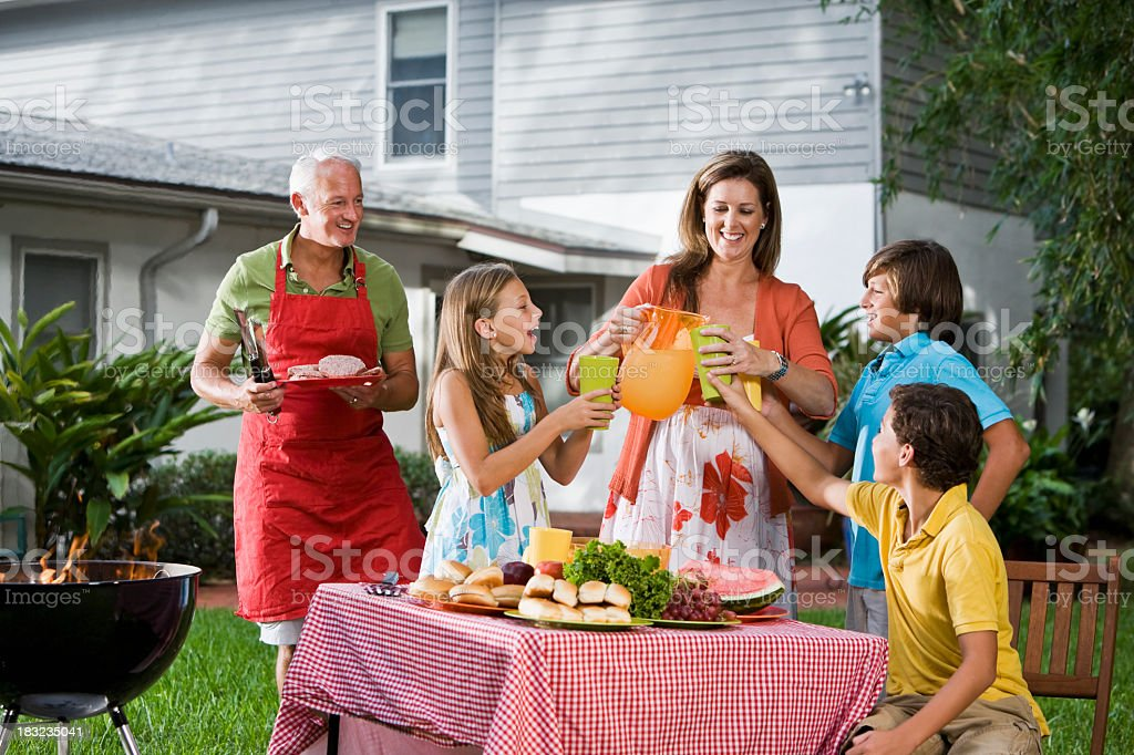 Family at backyard picnic table pouring lemonade royalty-free stock photo