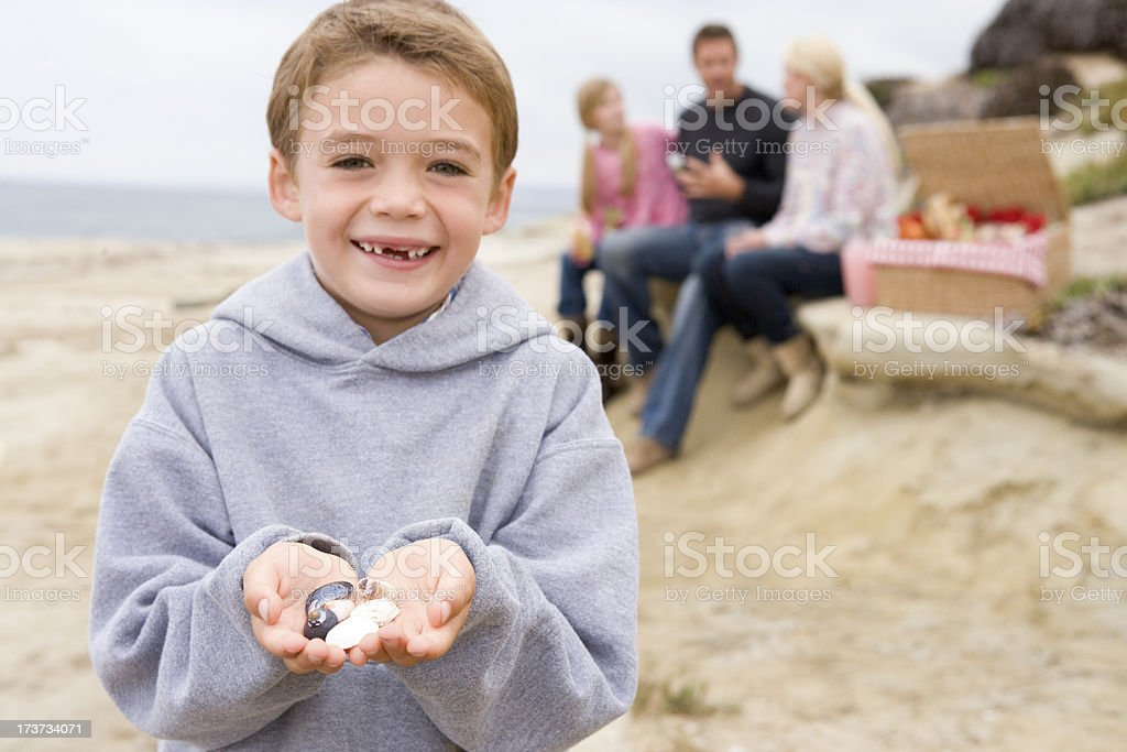 Family at beach with picnic smiling focus on boy royalty-free stock photo