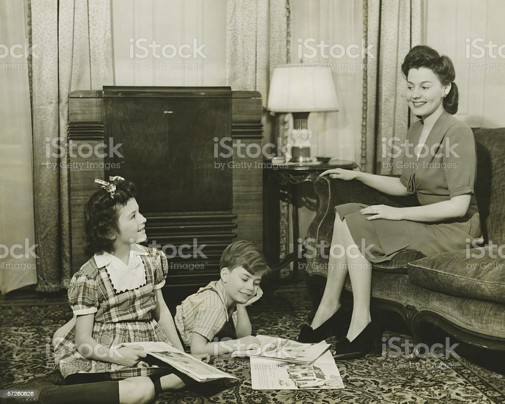 Family at home, children (6-7) (10-11) playing on carpet, mother sitting on sofa, (B&W) royalty-free stock photo