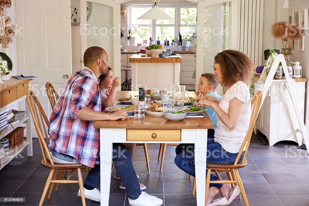 Family At Home Eating Meal In Kitchen Together stock photo
