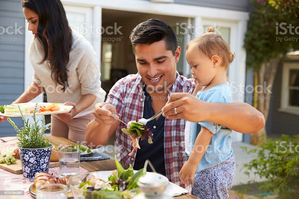 Family At Home Eating Outdoor Meal In Garden Together stock photo