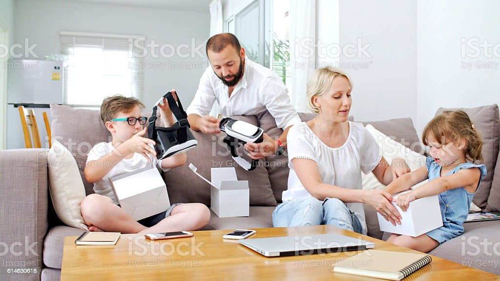 Family at home playing with virtual reality headsets. VR. stock photo