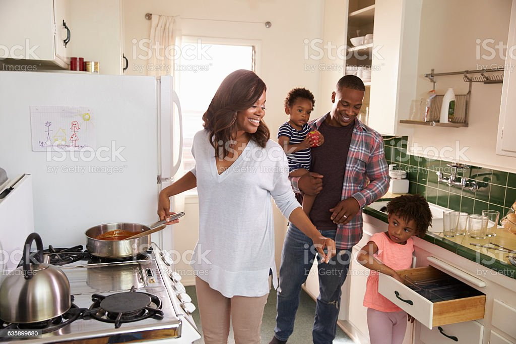 Family At Home Preparing Meal In Kitchen Together stock photo