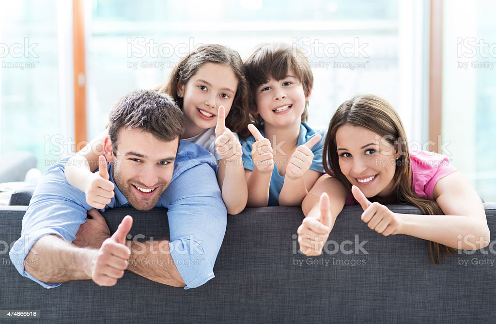 Family at home with thumbs up stock photo