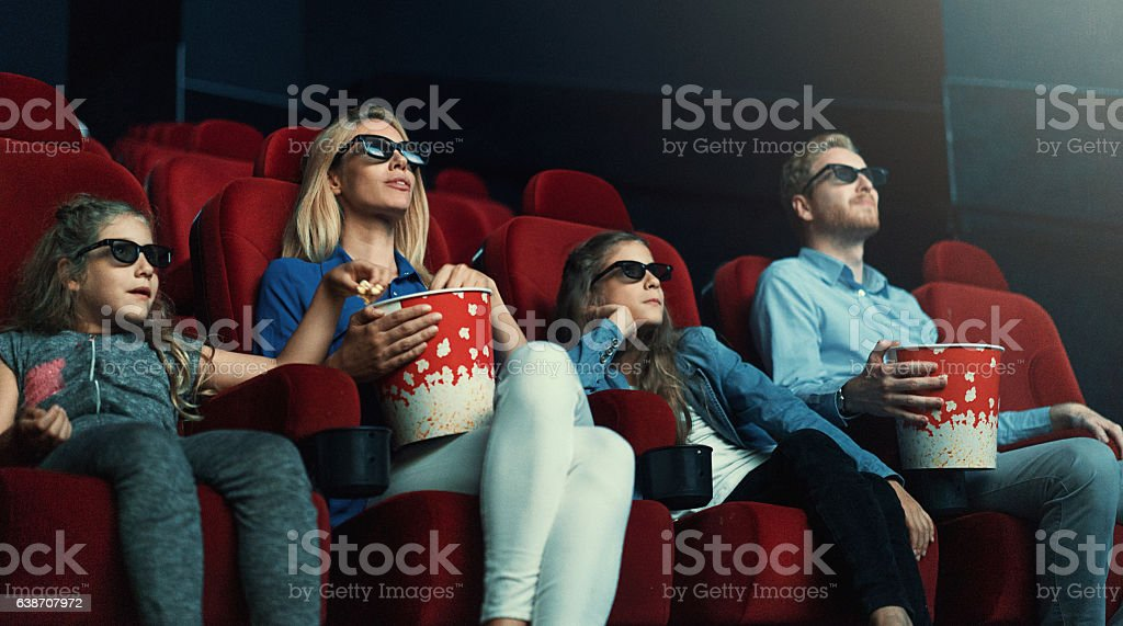 Family at movie theatre. stock photo