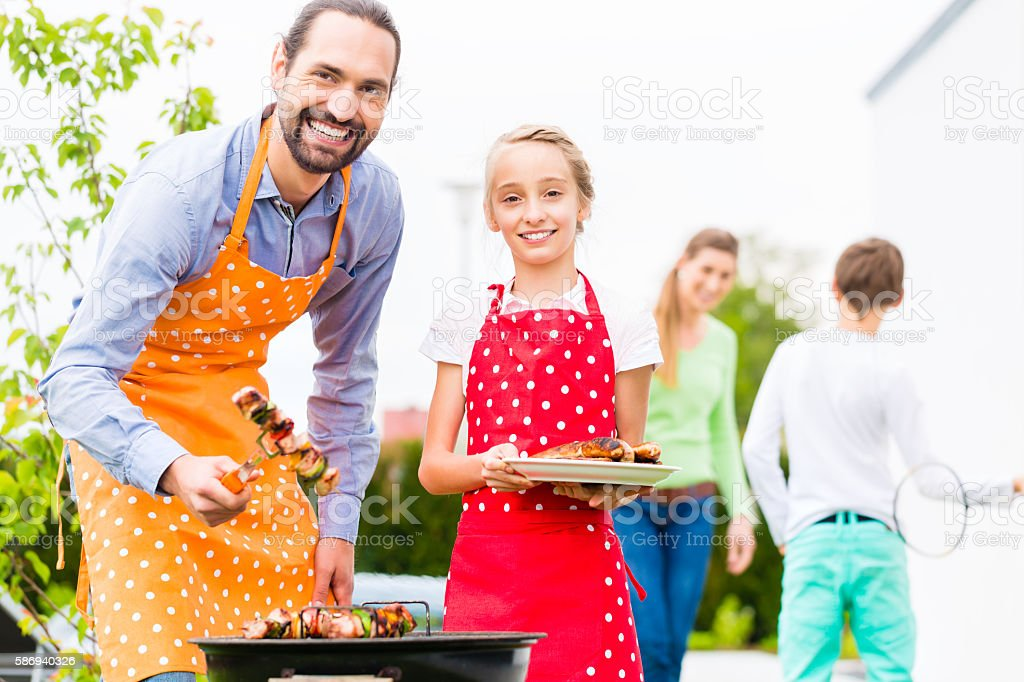 Family barbecue together in garden home stock photo