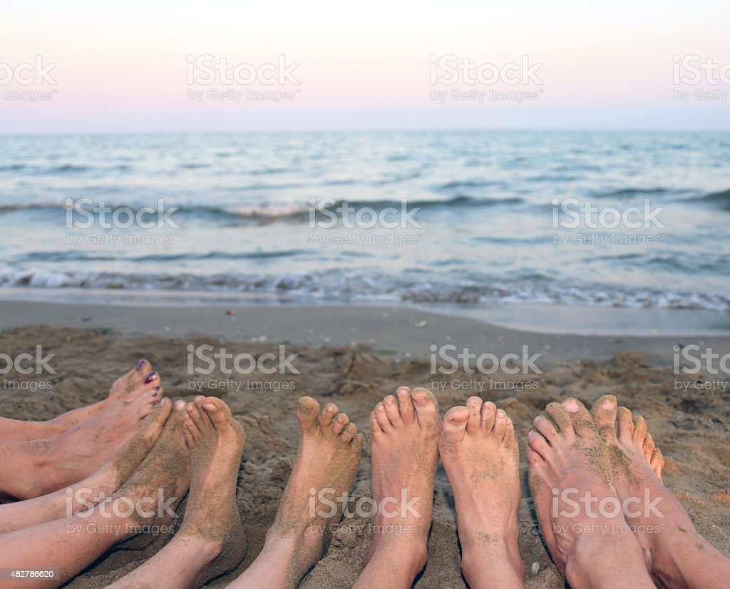 family barefoot by the sea on the beach stock photo