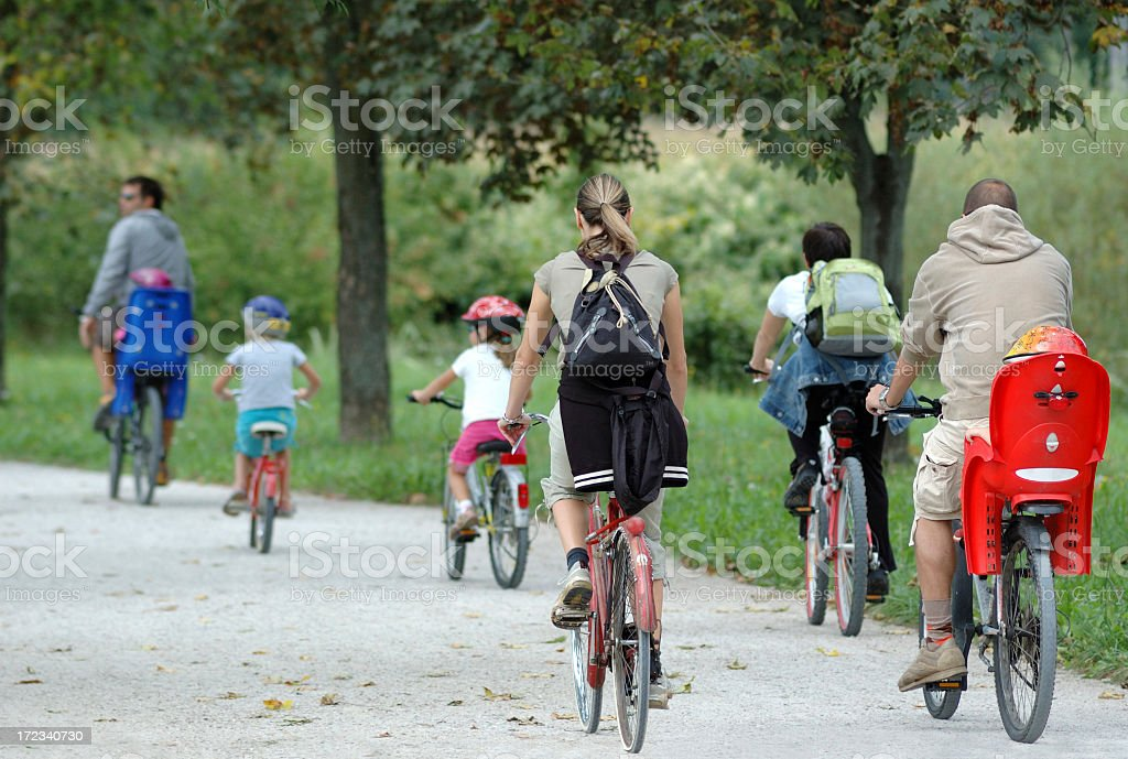 A family biking together in a park stock photo
