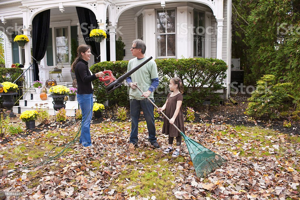family blowing and raking leaves stock photo
