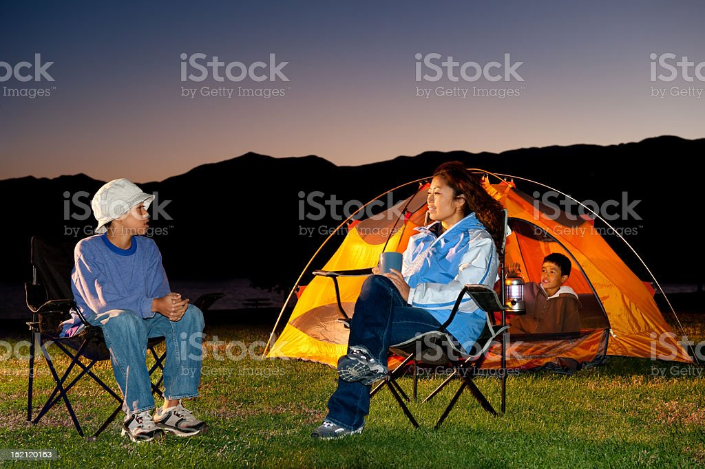 A family bonding while camping at night royalty-free stock photo