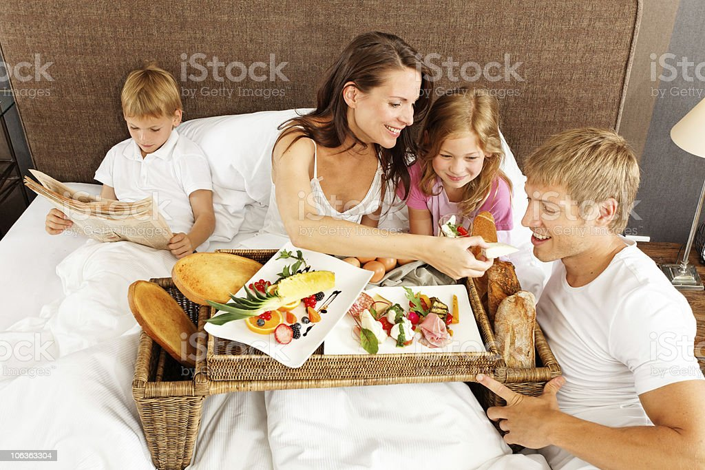 family breakfast in bed boy reading newspaper stock photo