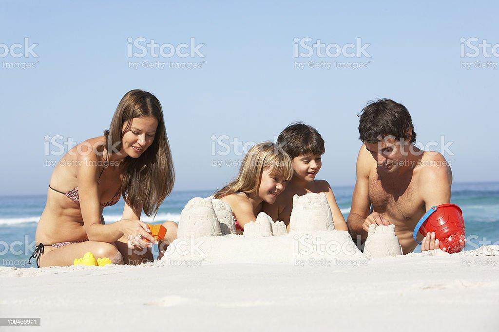 Family Building Sandcastles On Beach Holiday stock photo