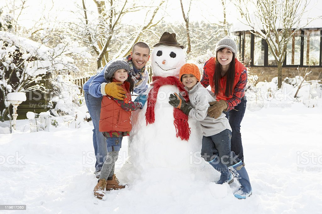 Family Building Snowman In Garden royalty-free stock photo