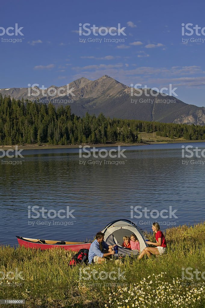 Family Camping on Mountain Lake with Canoe royalty-free stock photo