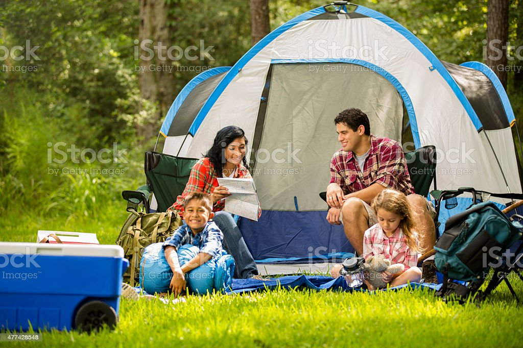 Family camping outdoors in forest. Tent, supplies. Summer vacation. stock photo