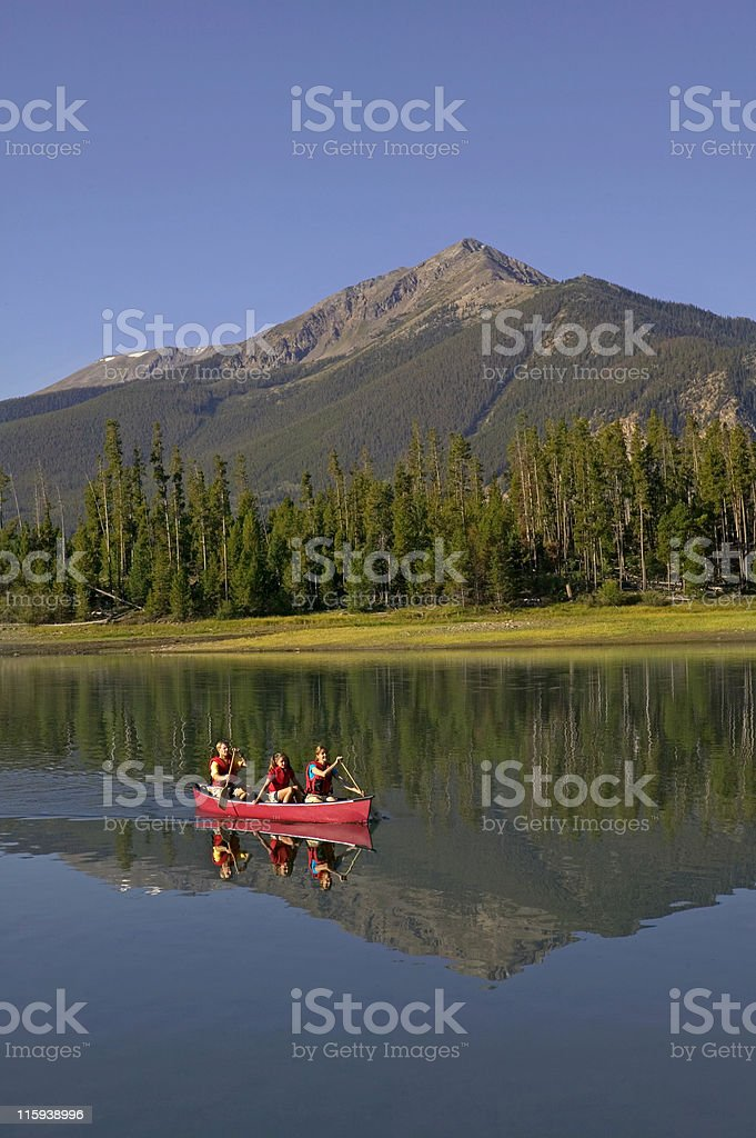 Family Canoeing on Mountain Lake with Reflection stock photo