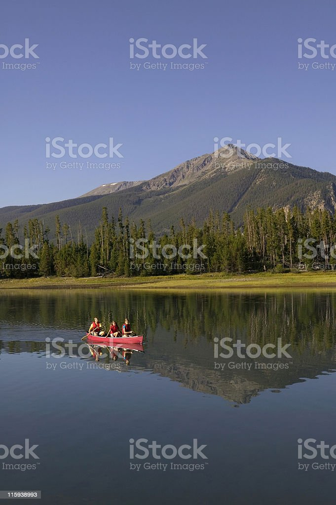 Family Canoeing With Mountains in Background royalty-free stock photo