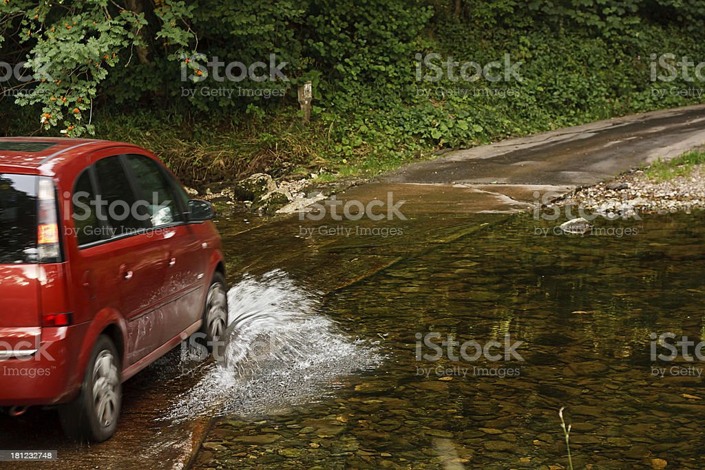 family car crossing a river at ford stock photo