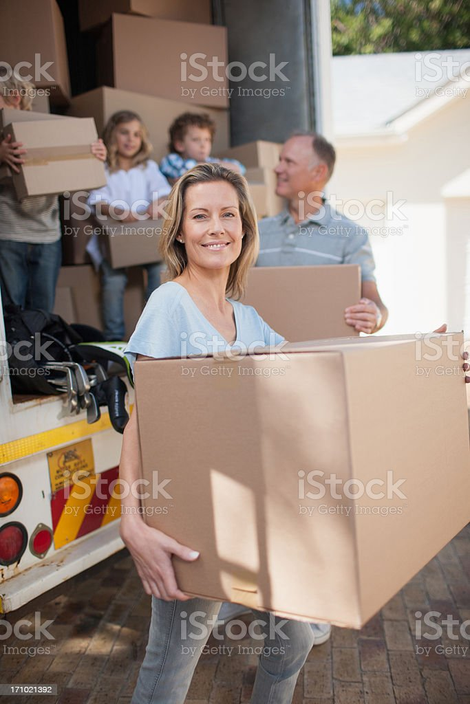 Family carrying boxes from moving van royalty-free stock photo