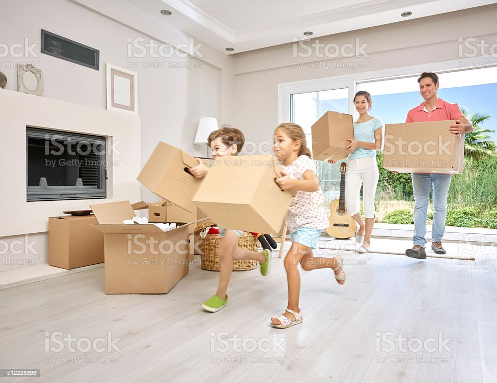 Family carrying large cardboard boxes into new home, portrait stock photo