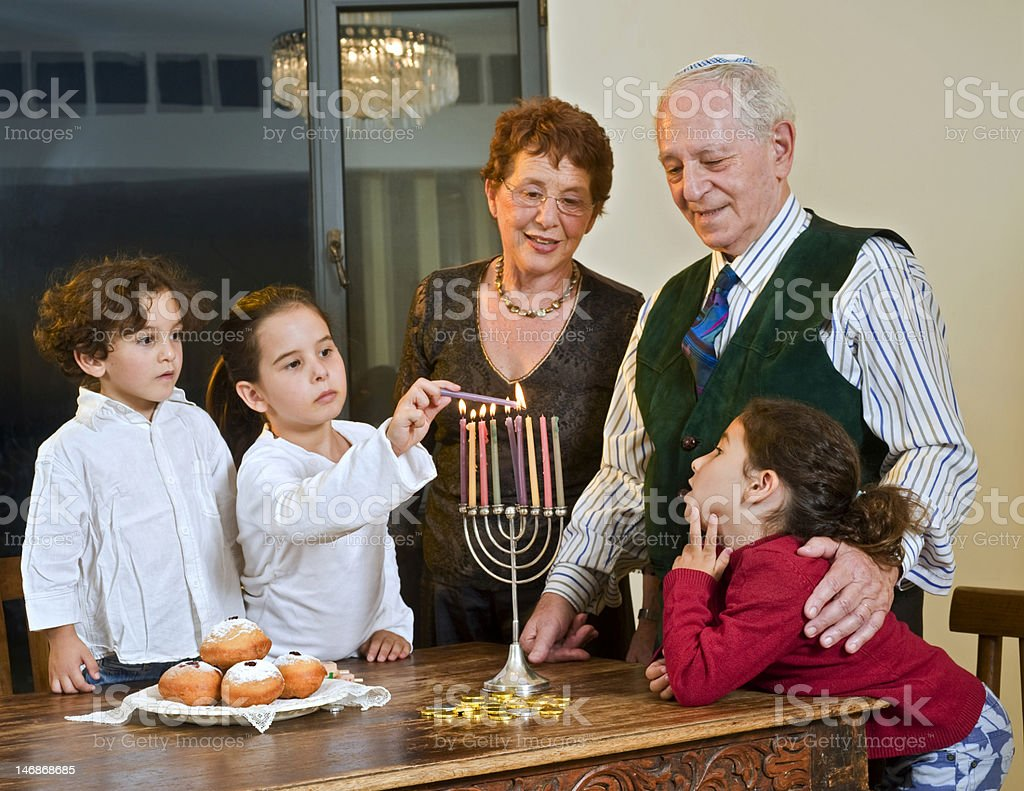 Family celebrating Hanukkah at their table at home stock photo
