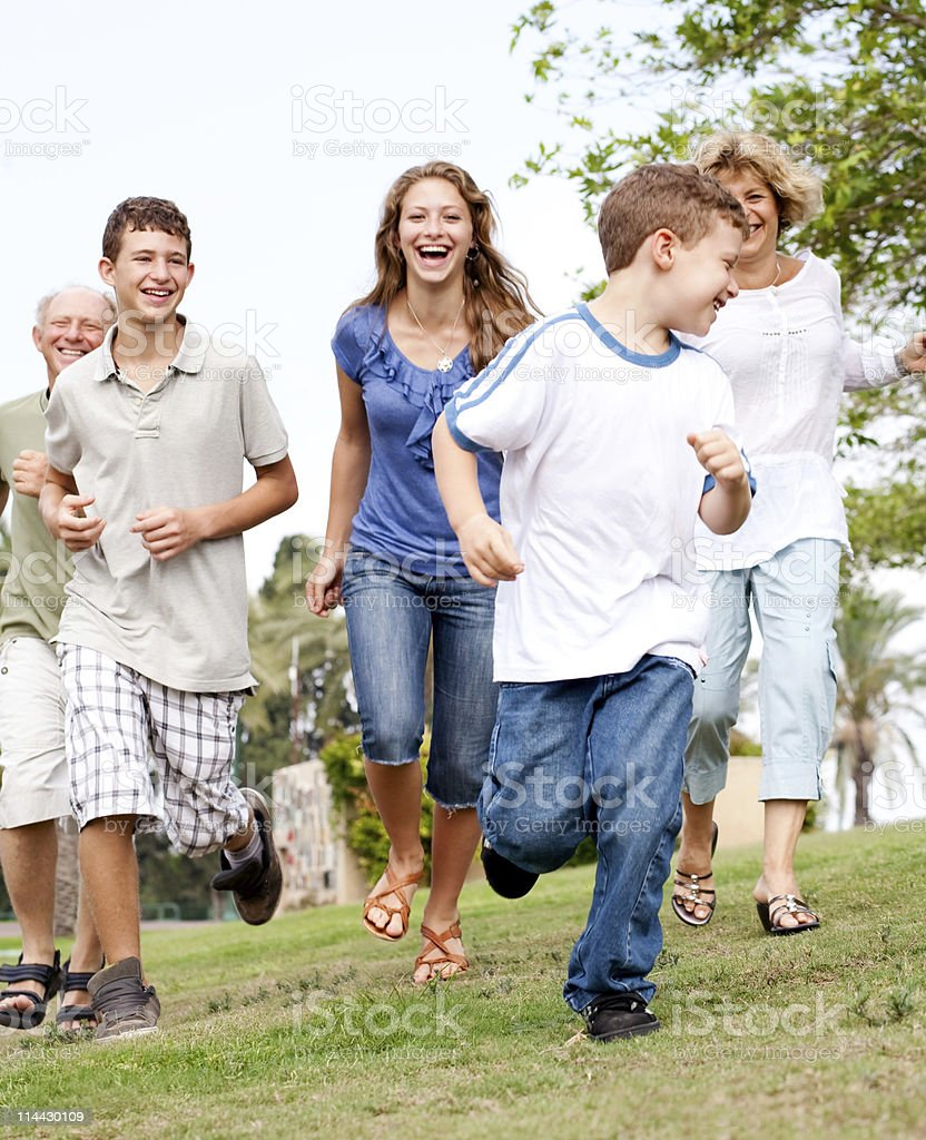 Family chasing young kid in the park royalty-free stock photo