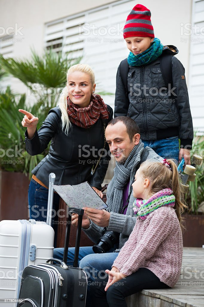 Family checking direction in map stock photo
