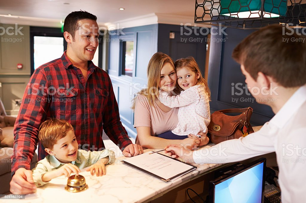 Family Checking In At Hotel Reception Desk stock photo