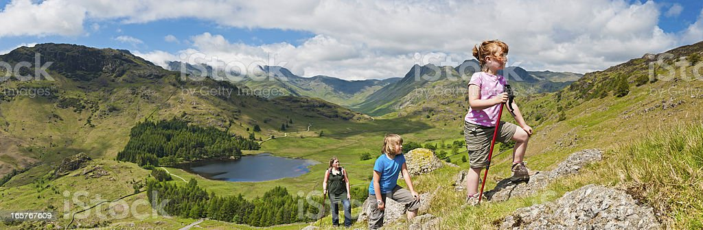 Family children climbing green mountain in idyllic landscape stock photo