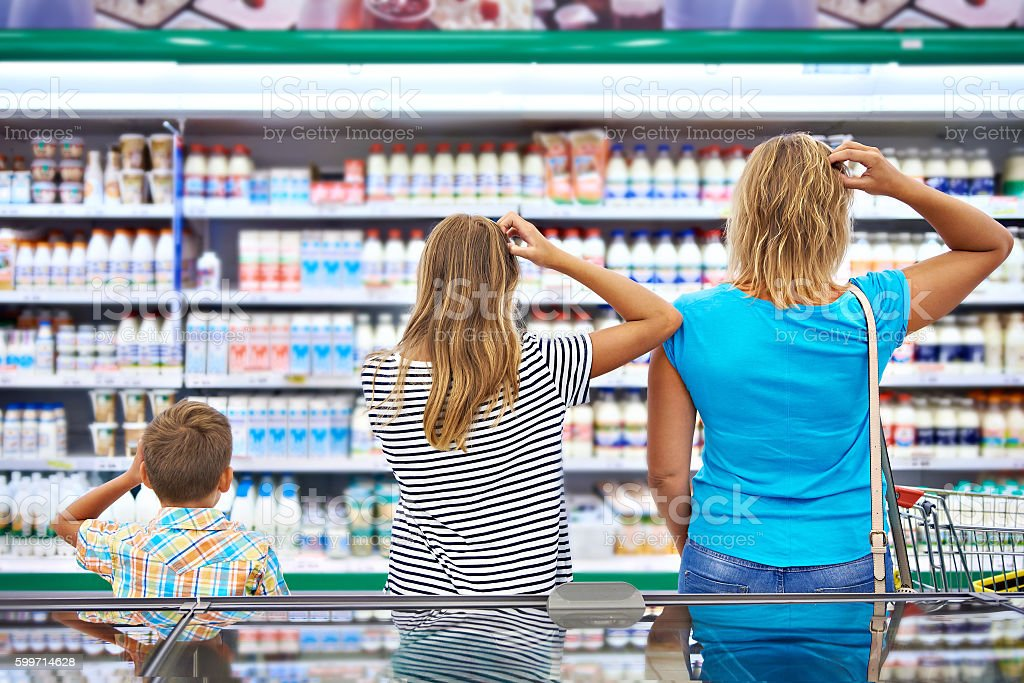 Family chooses dairy products in shop stock photo