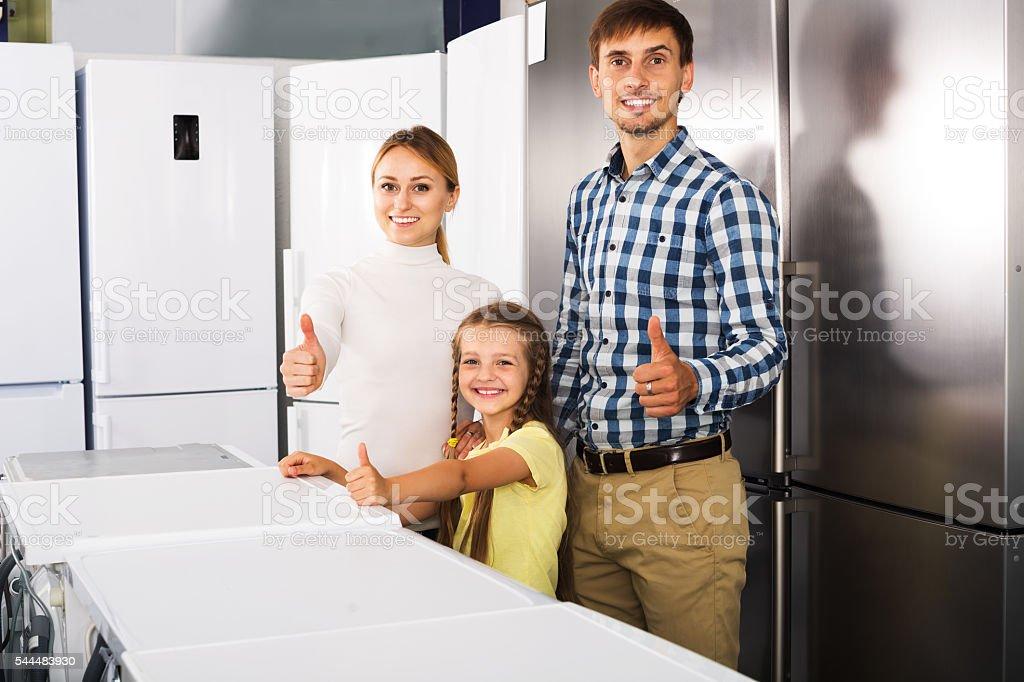 Family choosing refrigerator in store stock photo