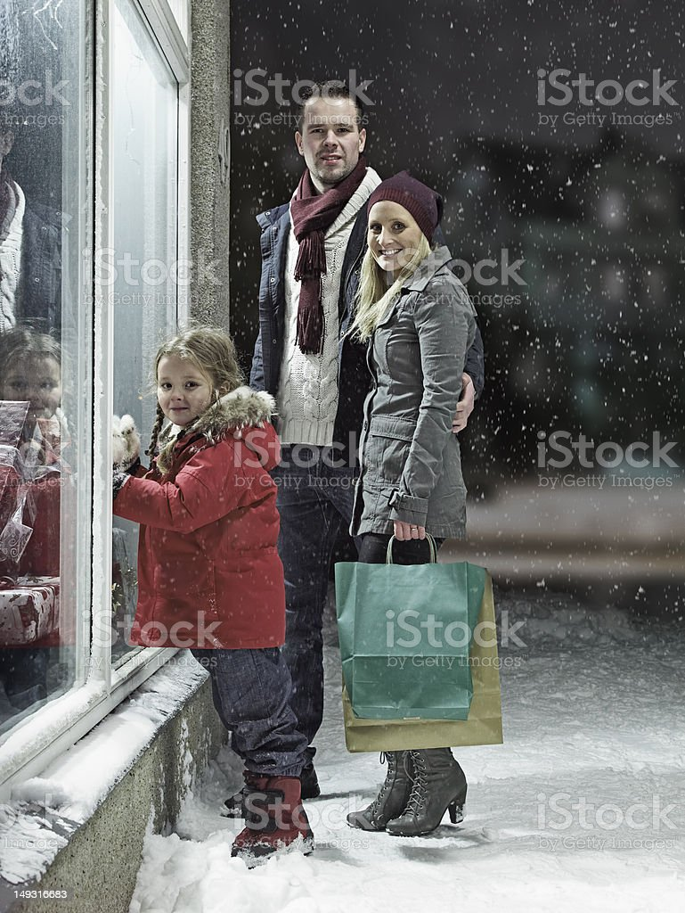 Family Christmas shopping in snow stock photo