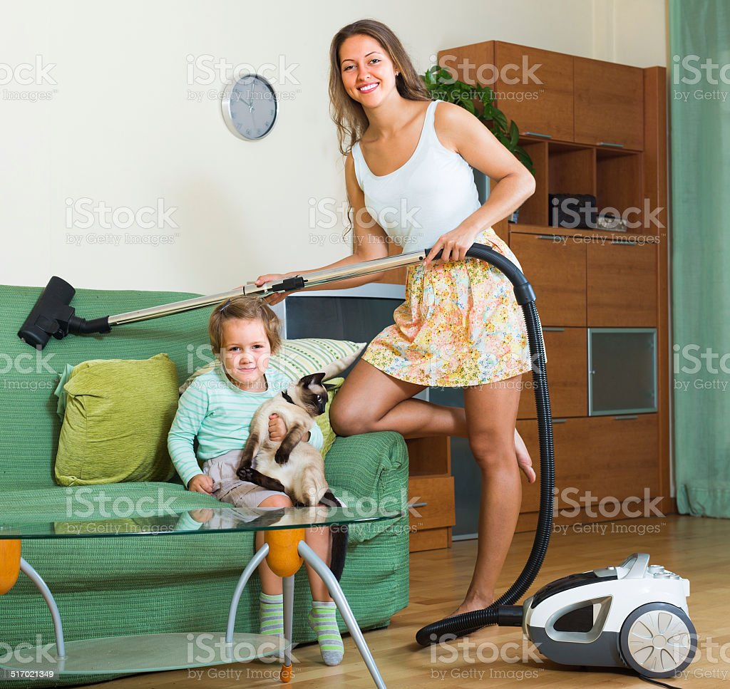 Family cleaning home with vacuum cleaner stock photo