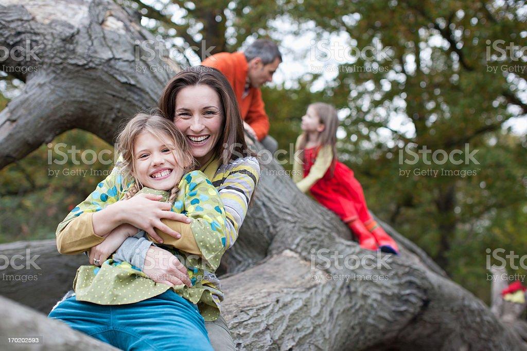 Family climbing on tree branch stock photo