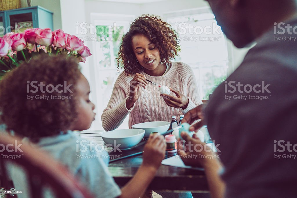 Family colouring Easter eggs at home stock photo