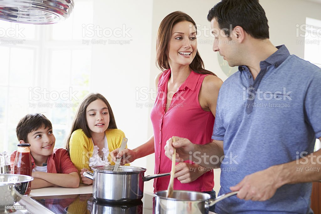 A family cooking a meal together stock photo