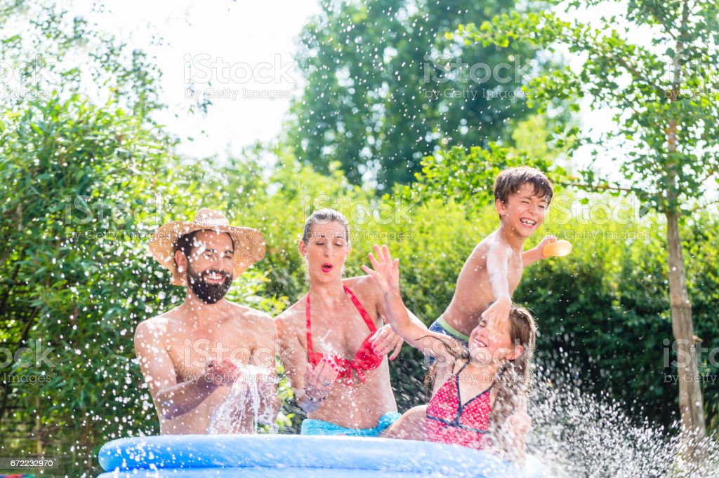 Family in garden pool splashing water cooling down, mother, father...