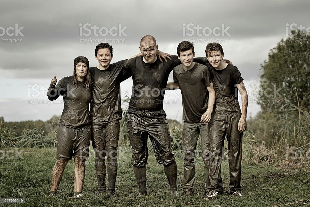 family covered by dirt during mud run stock photo