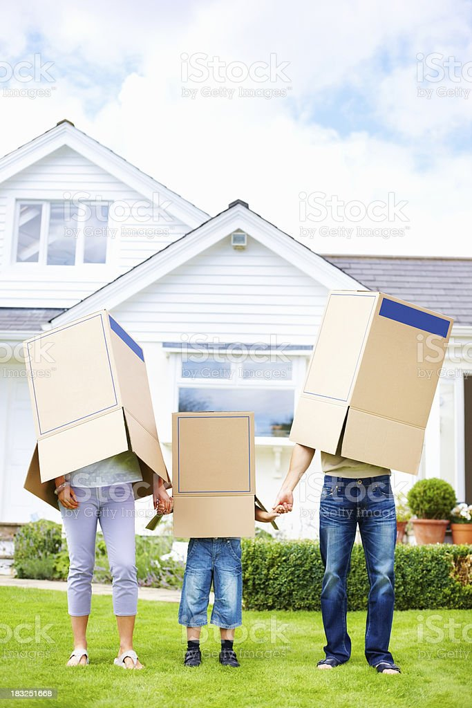 Family covering their faces with boxes in front of house royalty-free stock photo