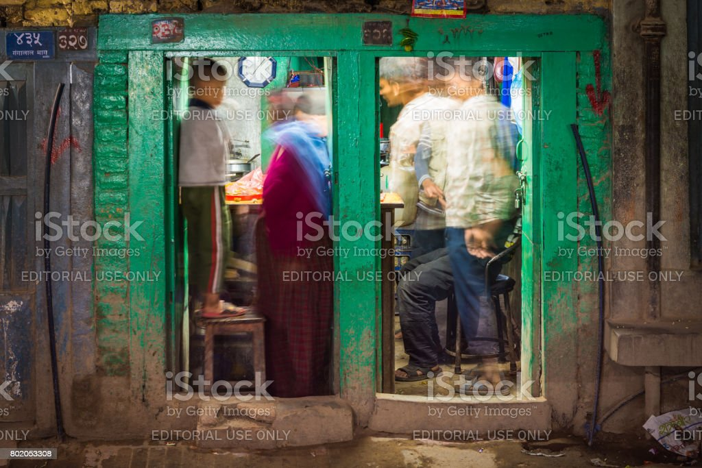 Family crowded into roadside retaurant kitchen at night Kathmandu Nepal stock photo