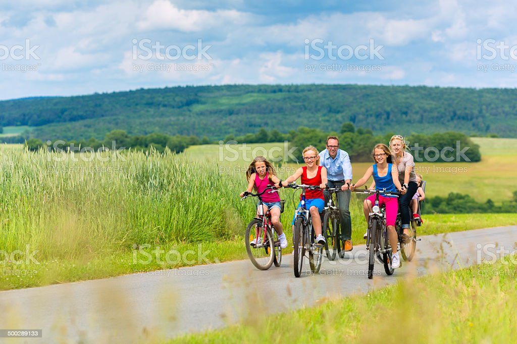Family cycling  in rural landscape stock photo
