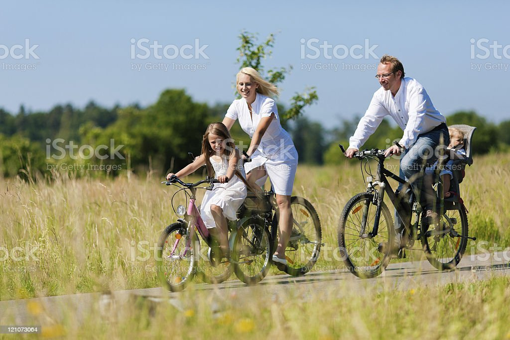 Family cycling outdoors in summer royalty-free stock photo