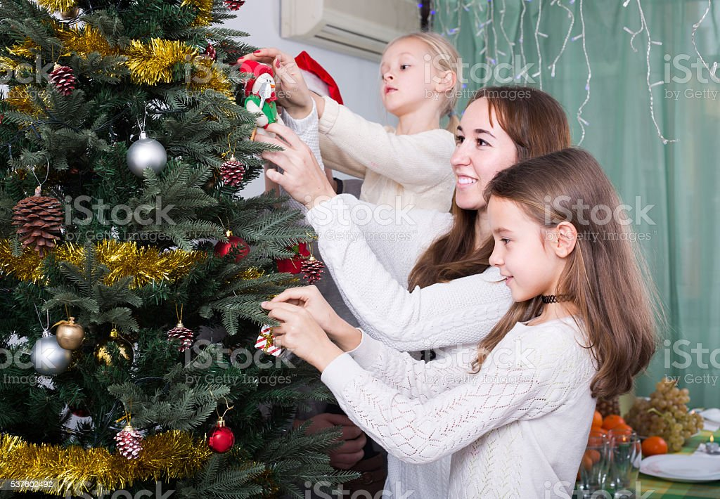 Family decorating Christmas tree at home stock photo