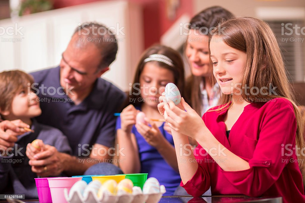 Family decorating Easter eggs at home. stock photo