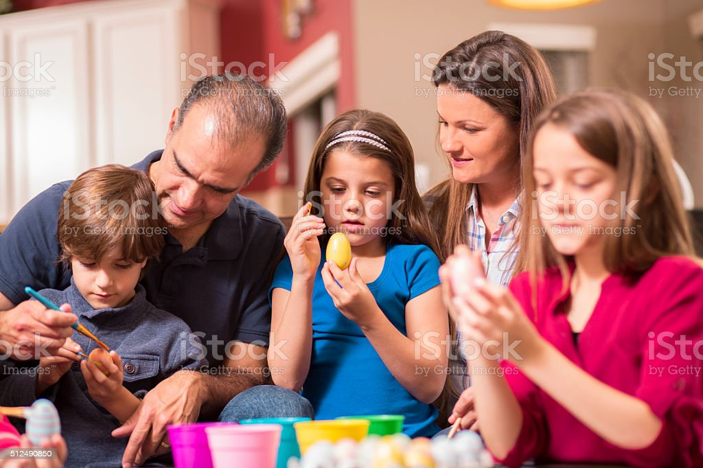 Latin descent family of five decorating Easter eggs together at home....
