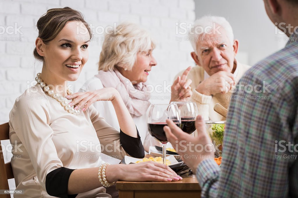 Family discussing at dinner time stock photo